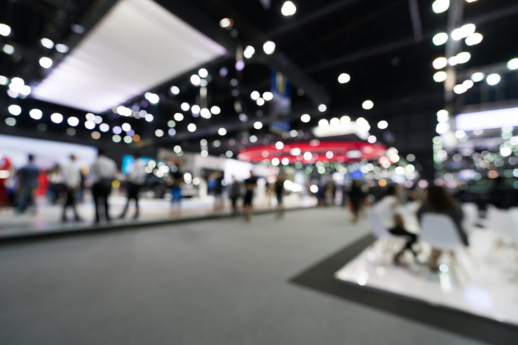 Blurred, defocusead background of public event exhibition hall. Business trade show or commercial activity concept